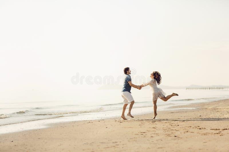 Det förälskade lyckliga paret har gyckel på stranden Dem att hoppa, skratta och tycka om havet royaltyfria bilder