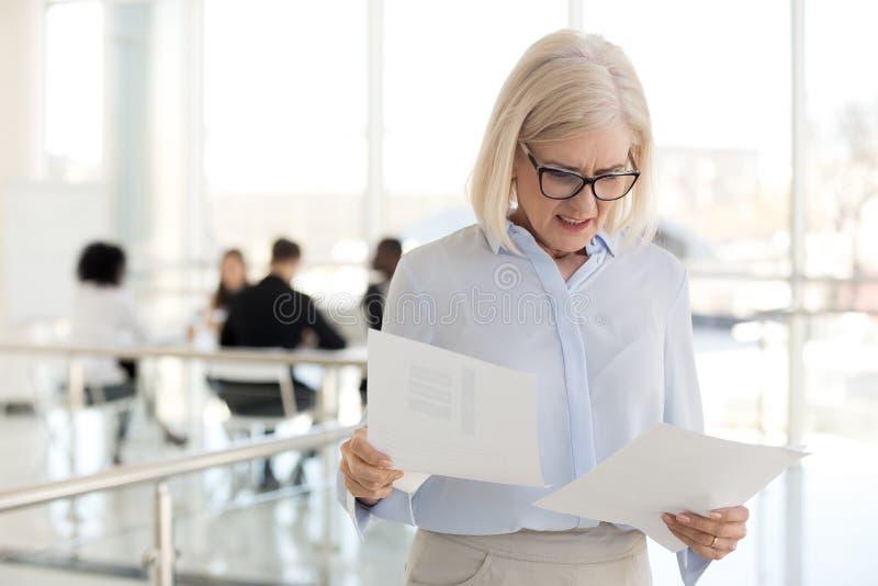 Det förargade mellersta åldriga affärskvinnaläsningmeddelandet mottog dåliga nyheter royaltyfri bild