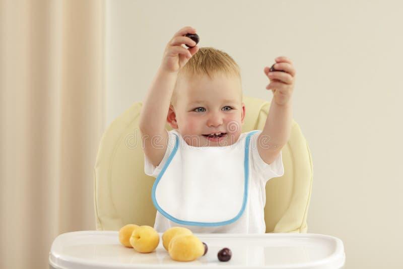 Det förtjusande lilla barnet som äter en aprikos behandla som ett barn in, stol mot den gråa bakgrunden royaltyfria foton