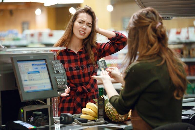 Det förvirrade anseendet för ung dam i supermarket shoppar royaltyfri bild