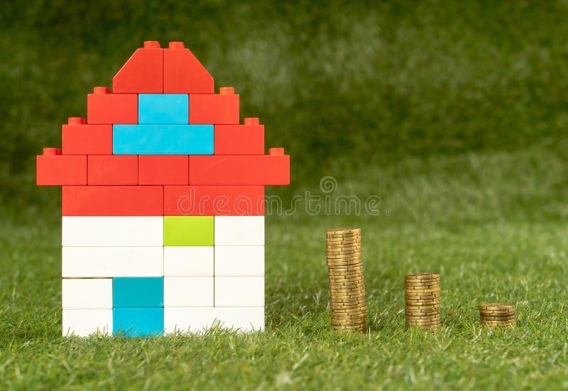 Det f?rgrika leksakhuset och h?gar av mynt p? gr?s intecknar in besparing- och egenskapsinvesteringbransch arkivbilder