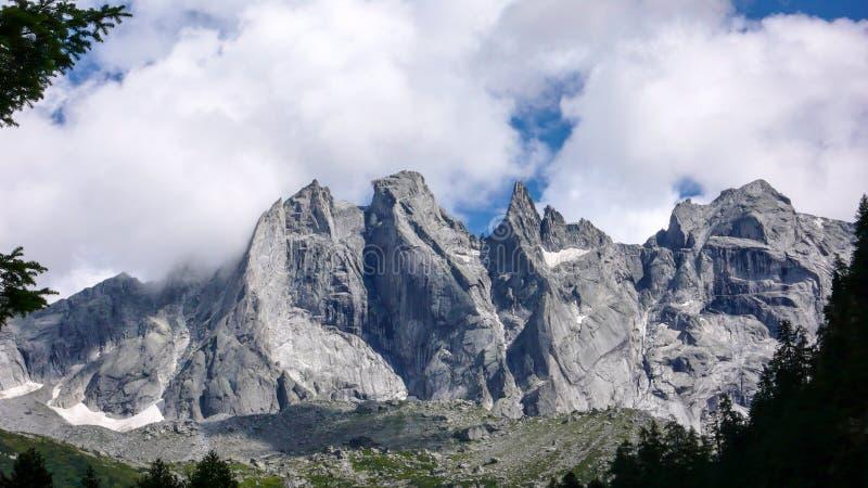 Det fantastiska berglandskapet i de schweiziska fjällängarna med ojämn skarp granit når en höjdpunkt under en molnig himmel royaltyfria foton