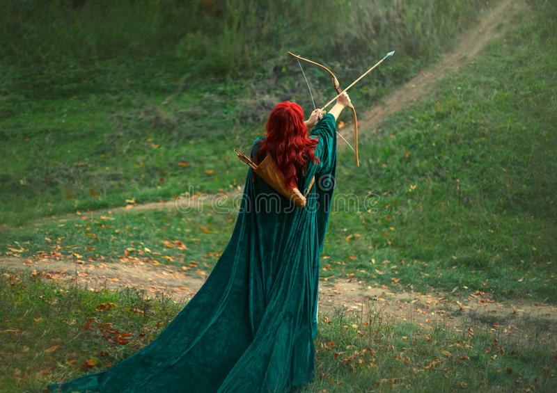 Det fantastiska teckenet, det ljusa fotoet, den bästa kvinnaskytten modigt och går modigt att jaga, den rödhåriga flickan är royaltyfria foton