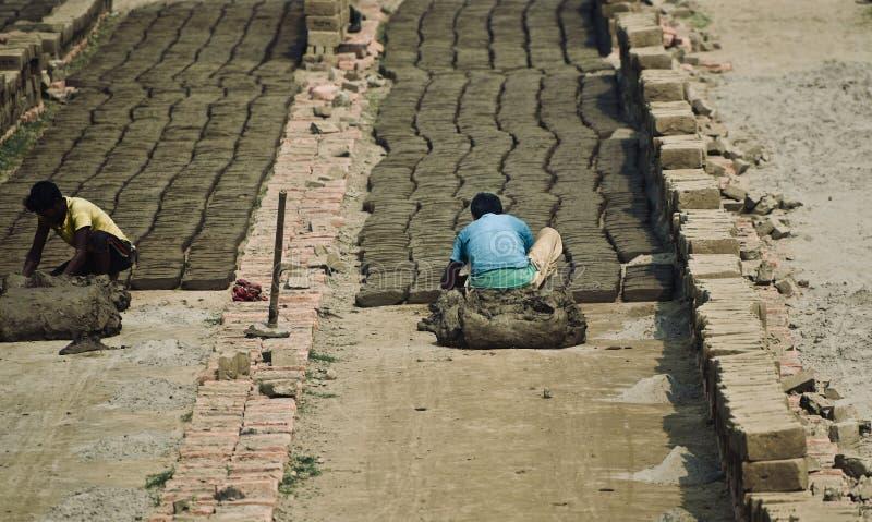 Det fattiga folket arbetar i ett tegelstenfält royaltyfri foto