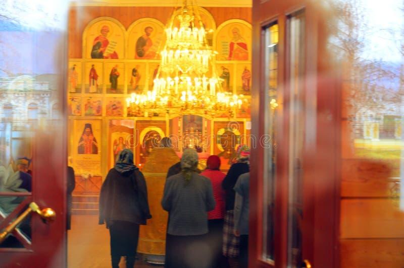 Det finns en tjänst i kyrkan Ljus brinner, folk står upp royaltyfria foton