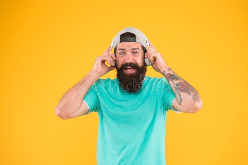 Det finns musik för varje man Skäggig man i moderiktig hipsterstil som ler på gul bakgrund Lycklig man med skägget och royaltyfria bilder