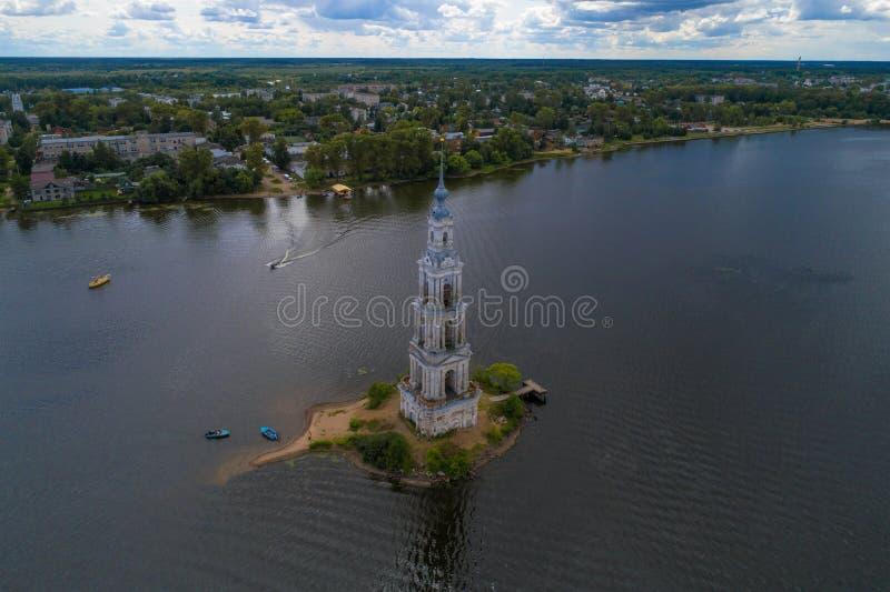 Det forntida översvämmade klockatornet mot bakgrunden av cityscapen Kalyazin Ryssland royaltyfria bilder