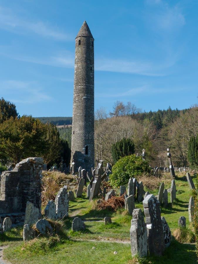 Det forntida runda tornet i kyrkogården på den historiska Glendalough kloster- platsen i ståndsmässiga Wicklow i Irland royaltyfri bild
