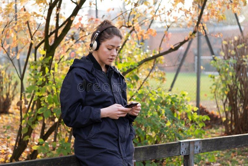Det fria för ung kvinna som lyssnar till musik med trådlös bluetoothhörlurar och den mobila smarta telefonen royaltyfria foton