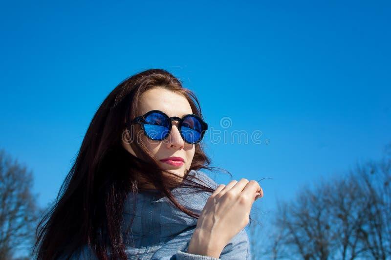 Det friacloseupstående av den härliga unga kvinnan med spegelförsedd solglasögon över blå himmel under tidig vårtid in arkivbilder