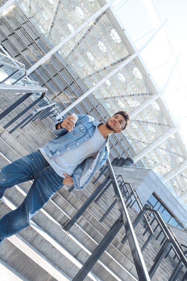 Det friafritid Mulattgrabbanseende på trappa med smartphonen som ser upp motiverad arkivbilder
