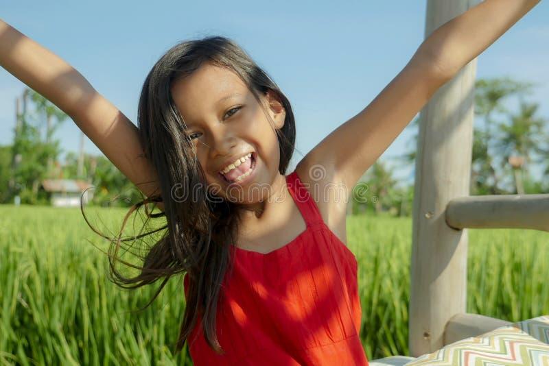 Det frialivsstilstående av härligt och sött le för ung flicka som är lyckligt och som är gladlynt, det iklädda upphetsade barnet  royaltyfria foton