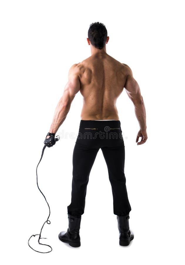 Det fulla kroppskottet av den muskulösa mannen med piskar och läderhandsken som ses från baksidan arkivbilder
