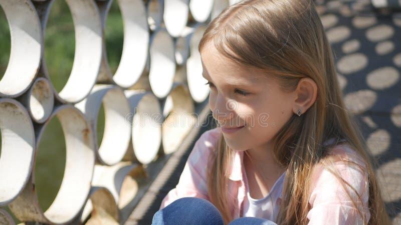 Det fundersamma barnet i parkerar, den utomhus- eftertänksamma lilla flickan, ledset leende på ungeframsida royaltyfria foton