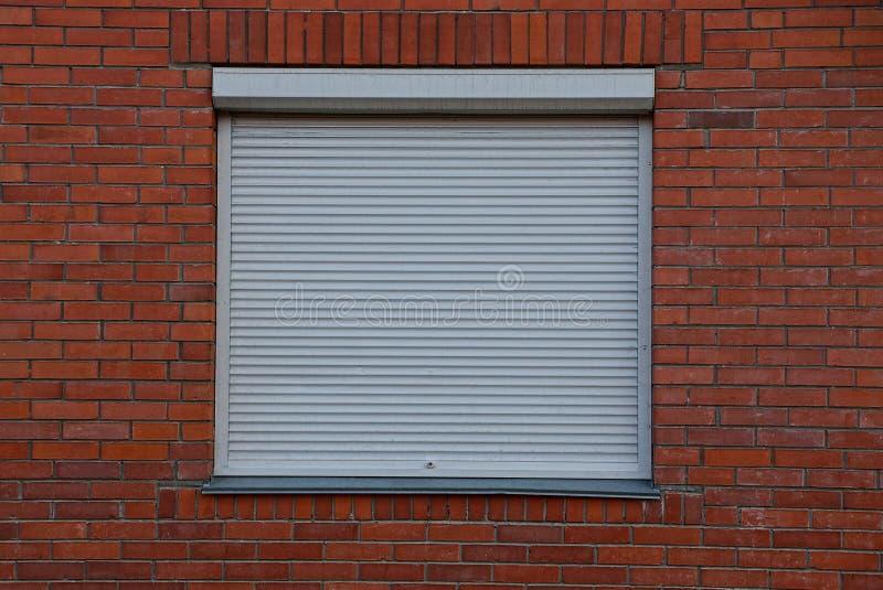 Det fyrkantiga fönstret stängde sig vid den gråa jalousien på en tegelstenvägg arkivfoton