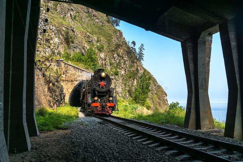 Det gamla ångadrevet lämnar tunnelen på denBaikal järnvägen royaltyfri foto