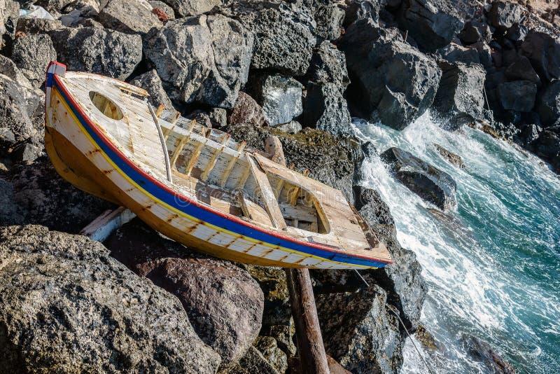 Det gamla övergav träfartyget som kraschas på, vaggar av den Santorini ön royaltyfri bild