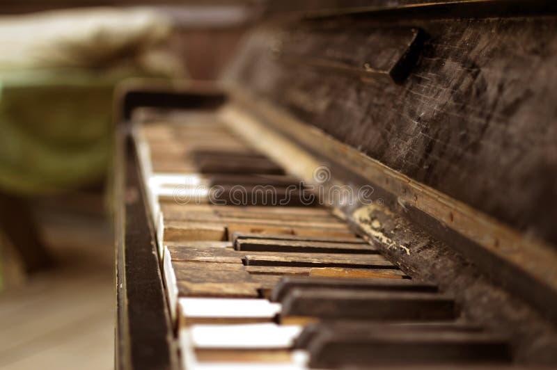 Det gamla brutna pianot i trähuset royaltyfri foto