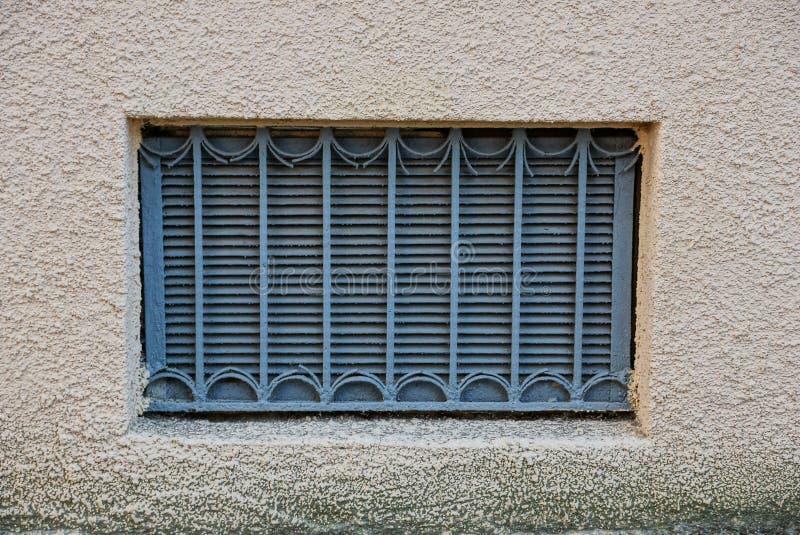 Det gamla fönstret med ett galler för grått järn på en brun betongvägg arkivfoto