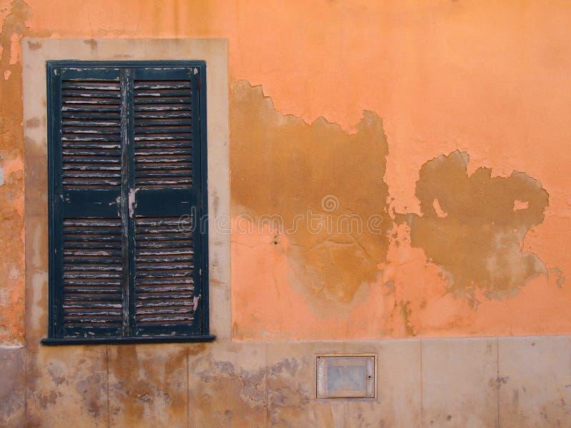 Det gamla fönstret med gröna målade stängda träslutare på en orange medelhavs- ockra färgade sprucken skalande flagnande wa för a royaltyfria foton