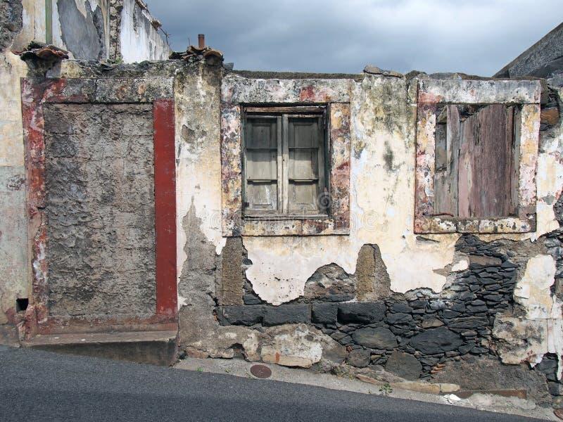 Det gamla förstörda huset kollapsade delvis på en slutta gata med en blockerad övre dörr som smular väggar och bleknar röda målad arkivfoto
