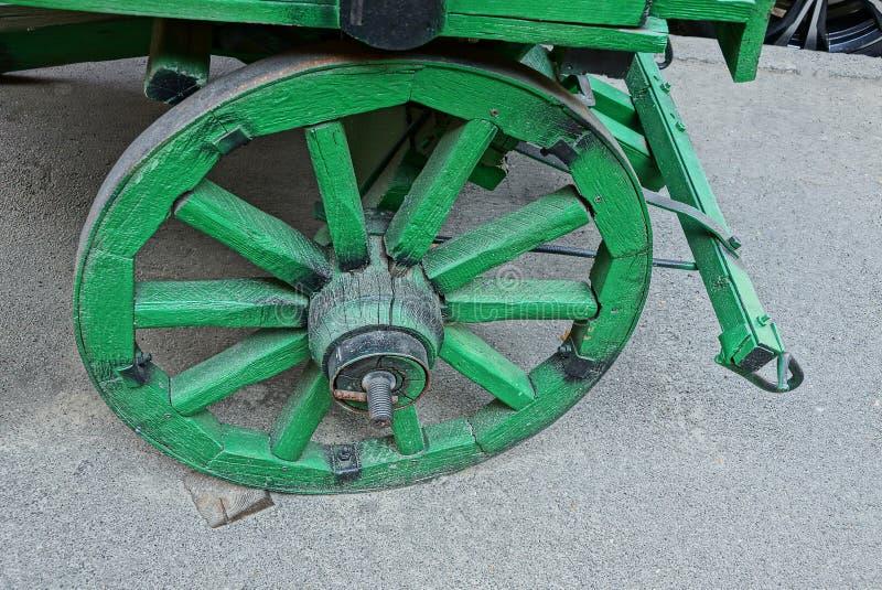 Det gamla gröna trähjulet av vagnen står på den gråa asfalten på gatan arkivfoton