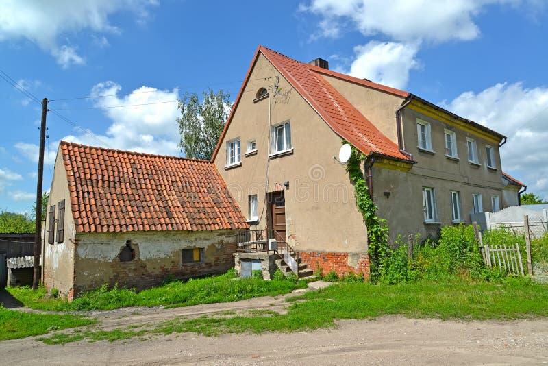 Det gamla lägenhethuset med det fäste skjulet på Karl Marx Street Gvardeysk Kaliningrad region royaltyfria foton