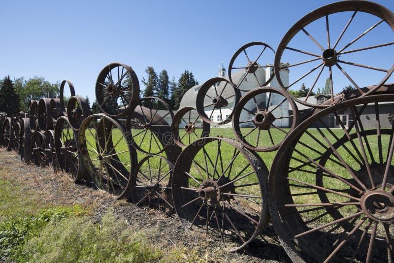 Det gamla lantgårdstaketet som göras av gamla rostiga vagn- & traktorhjul på hantverkarna på den Dahmen ladugården, är på Palouse arkivbilder