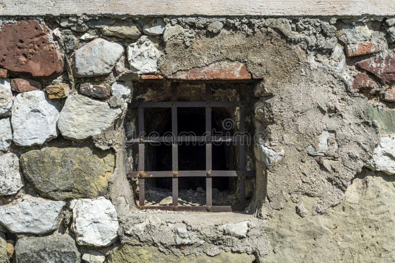 Det gamla lilla fönstret för fängelsecellen med metallstänger och vaggar tegelstenväggen arkivbilder