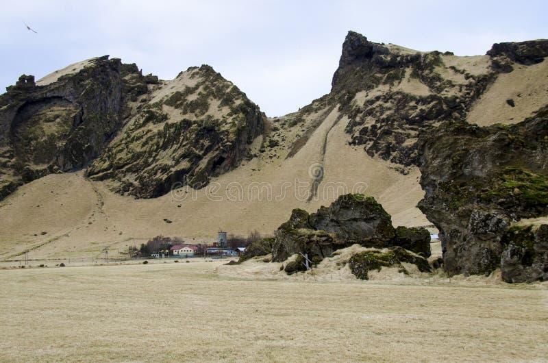 Det gamla stenhuset f?rst?rde den forntida vikingen som var bevuxen med gult torrt gr?s i Island arkivfoto