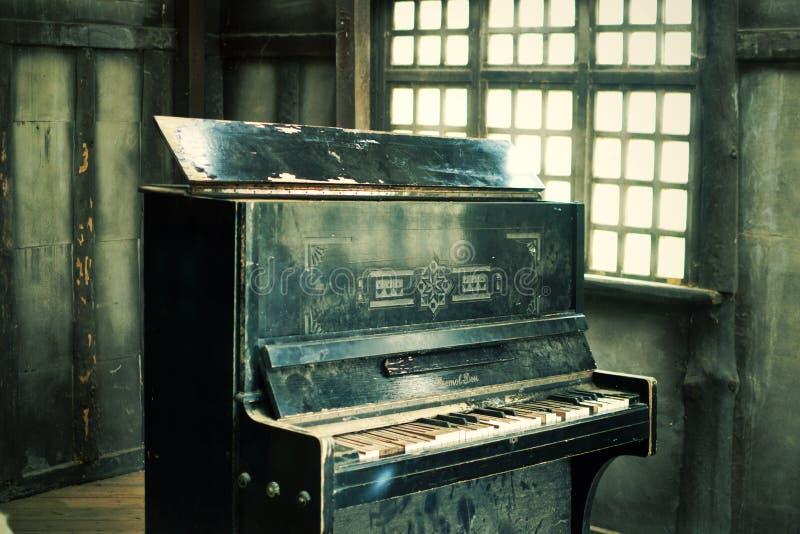 Det gamla svarta brutna pianot arkivfoto