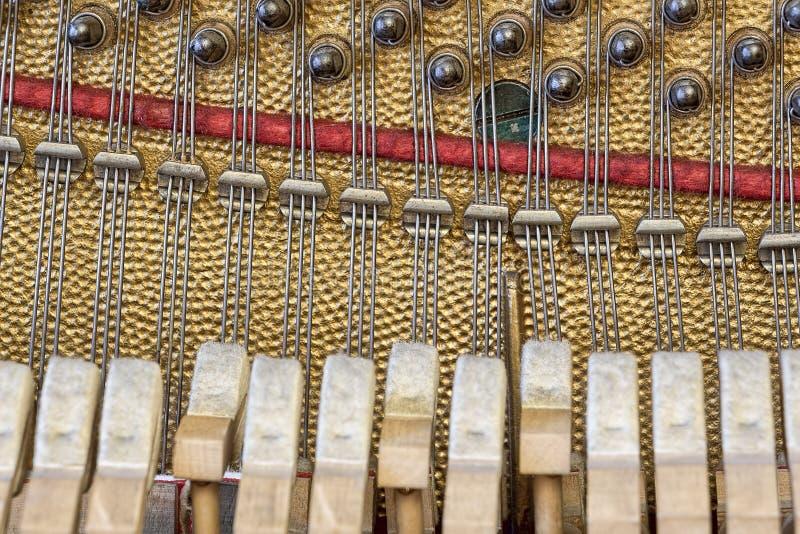 Det gamla tappningpianot inom, stränger och hammare arkivfoton