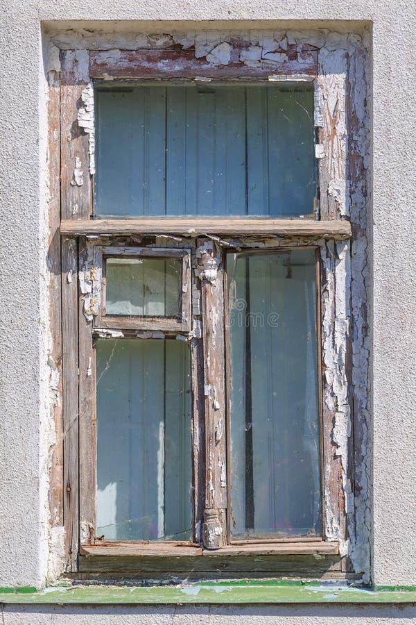 Det gamla träfönstret med ett lufthål förser med rutor och restna av vit målarfärg på väggen royaltyfria foton