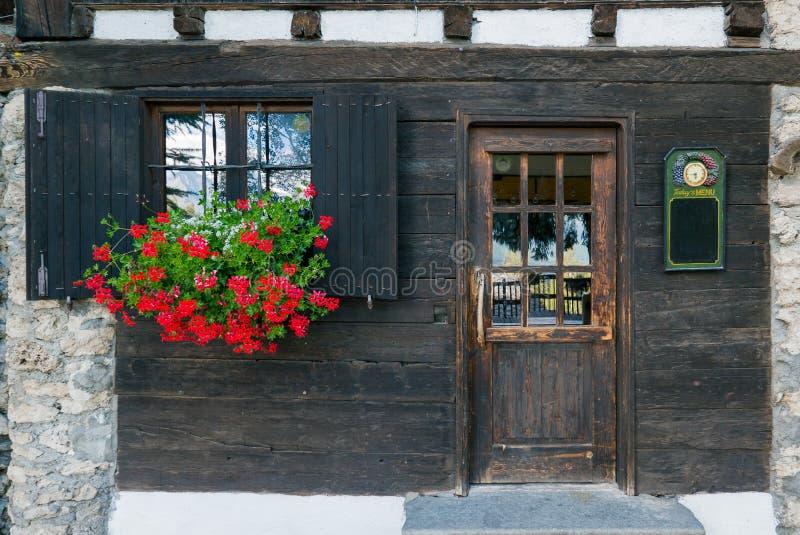 Det gamla träfönstret med slutare och blommor near gammal trädoo arkivbilder