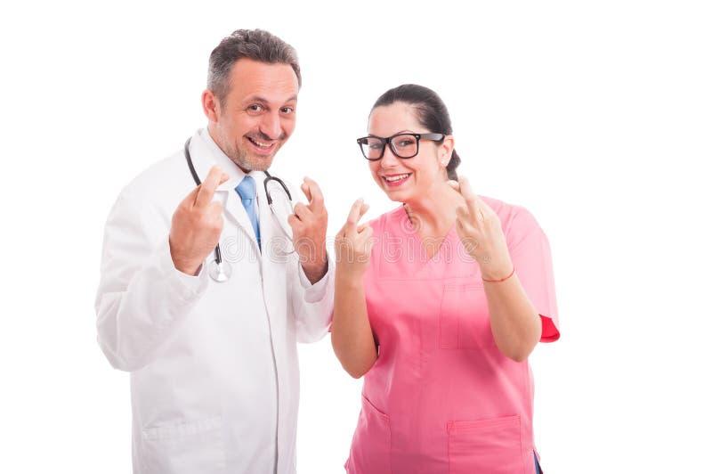 Det glade medicinska laget indikerar tecknet för bra lycka arkivbilder