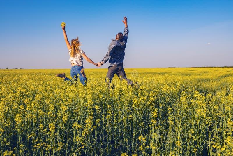 Det glade paret med öppna armar hoppar på fältet arkivbild