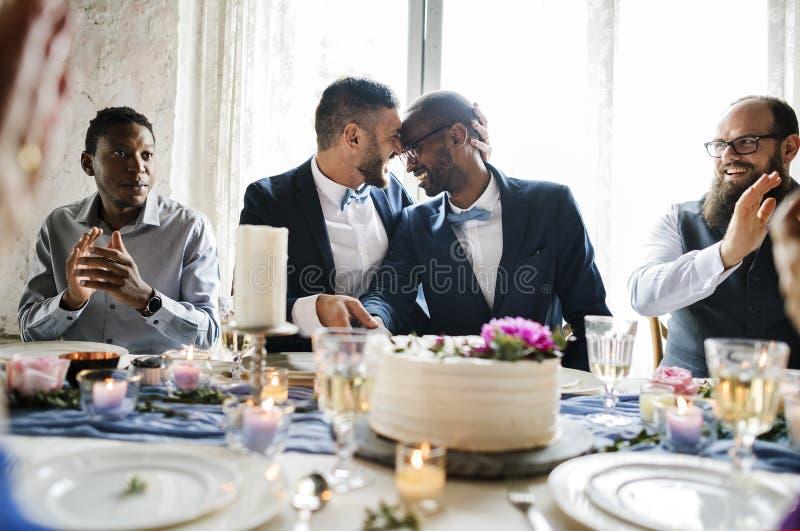 Det glade paret räcker den bitande bröllopstårtan royaltyfri fotografi
