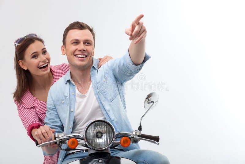 Det gladlynta barnet som älskar par, kör mopeden royaltyfri foto