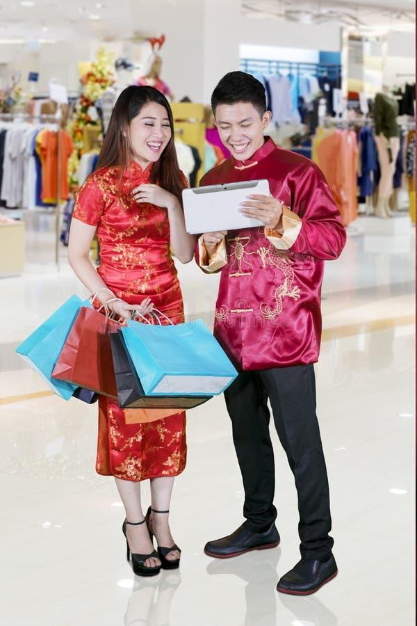 Det gladlynta paret shoppar direktanslutet med minnestavlan royaltyfri bild