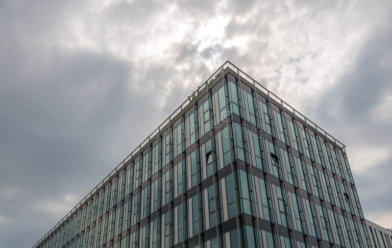 Det Glass kontorsbyggnadslutet sköt upp, regnmoln på bakgrunden arkivfoto