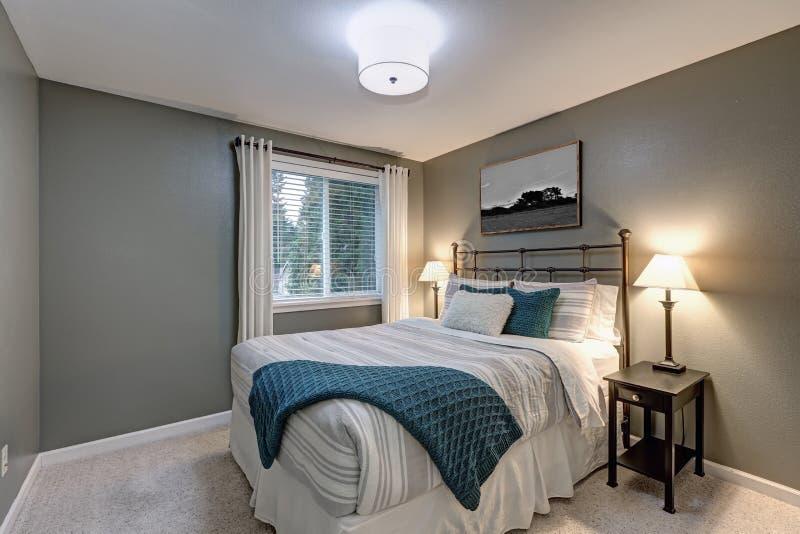 Det gråa sovrummet skryter stor järnsäng arkivfoton