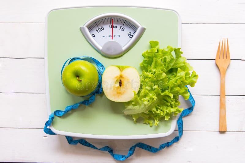 Det gröna äpplet, den nya grönsaken med viktskalan och mätabandet för det sunt bantar bantning royaltyfria foton