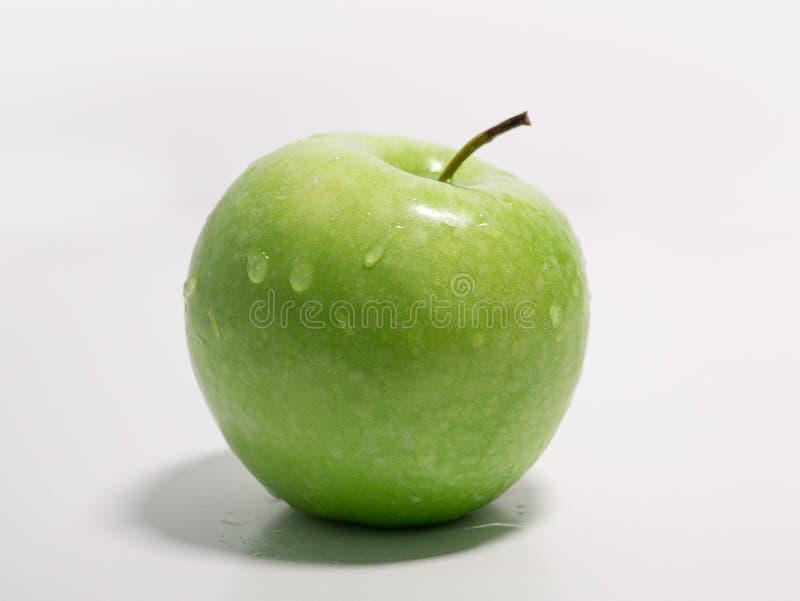 Det gröna äpplet med vatten tappar på vit bakgrund Slapp fokus royaltyfria bilder