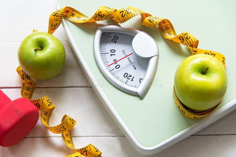 Det gröna äpplet med viktskalan och mätabandet för det sunt bantar bantning royaltyfria bilder