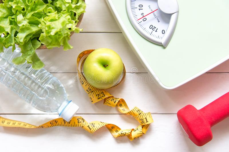 Det gröna äpplet och viktskalan, måttklappet med den nya grönsaken, rent vatten och sportutrustning för kvinnor bantar bantning B fotografering för bildbyråer