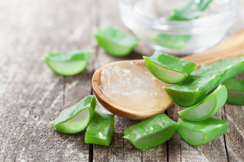 Det gröna aloevera bladet och nya stelnar i sked på trätabellen royaltyfria foton