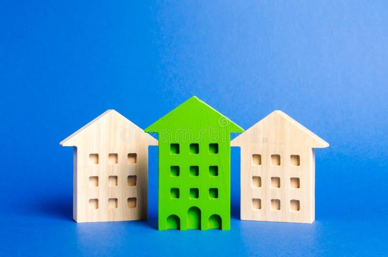Det gröna diagramet av en bostads- byggnad står bland vilar ut av husen Sökande för att det bästa alternativet ska köpa en lägenh royaltyfria foton