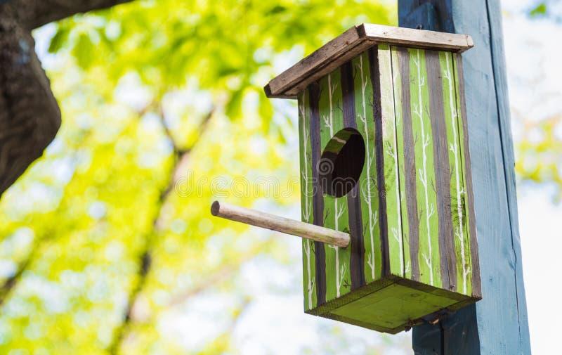 Det gröna fågelhuset hängde utanför arkivbild