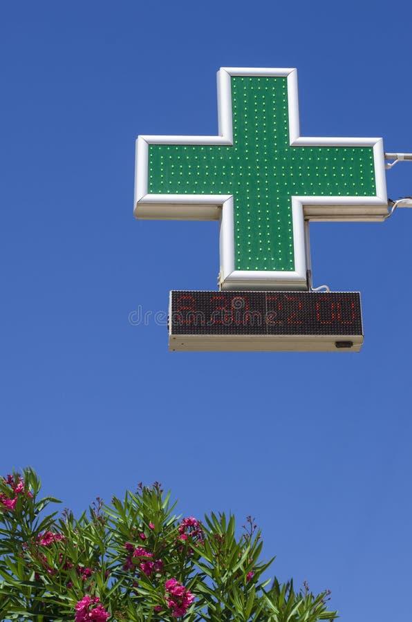 Det gröna korset symboliserar apoteket med arbetstiderna royaltyfri fotografi