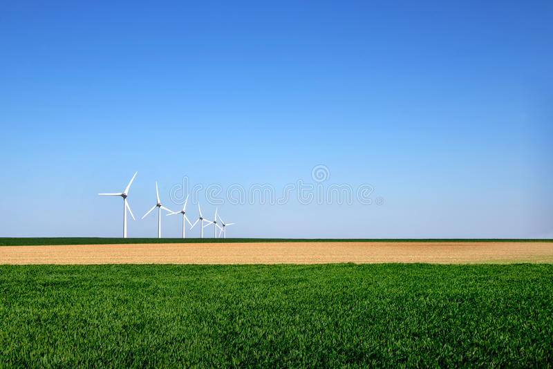 Det grafiska moderna landskapet av vindturbiner arrangera i rak linje i ett fält arkivbilder